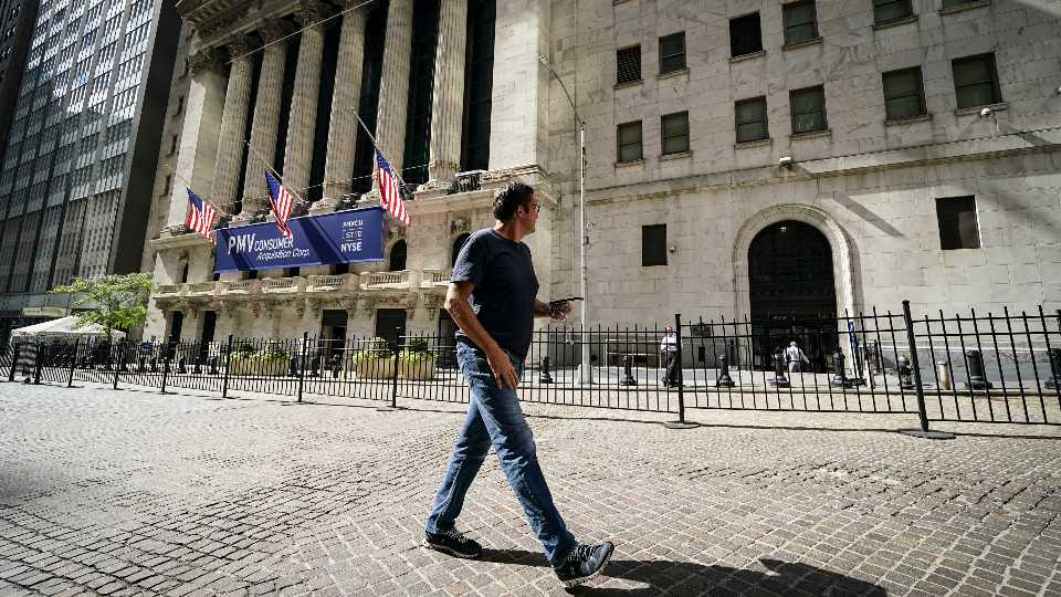 A pedestrian pass the New York Stock Exchange, Friday, Oct. 2, 2020, in New York. Stocks around the world are falling sharply Wednesday, Oct. 28, on worries the worsening pandemic will push governments to bring back restrictions on businesses.