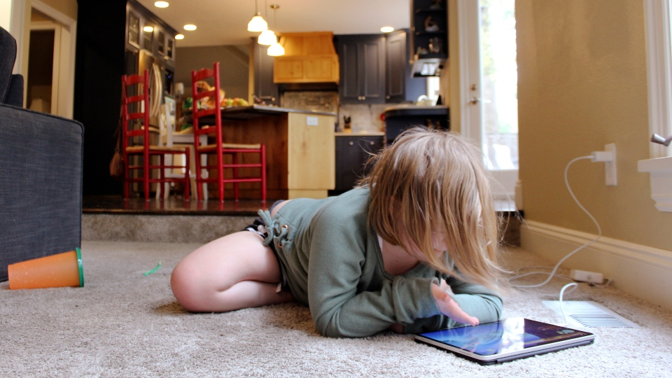 Lizzie Dale sprawls on the floor to play games on an iPad as her siblings work on school work in the kitchen behind her in their home in Lake Oswego, Ore., Oct. 30, 2020. In Oregon, one of only a handful of states that has required a partial or statewide closure of schools in the midst of the COVID-19 pandemic, parents in favor of their children returning to in-person learning have voiced their concerns and grievances using social media, petitions, letters to state officials, emotional testimonies at virtual school board meetings and on the steps of the state's Capitol.
