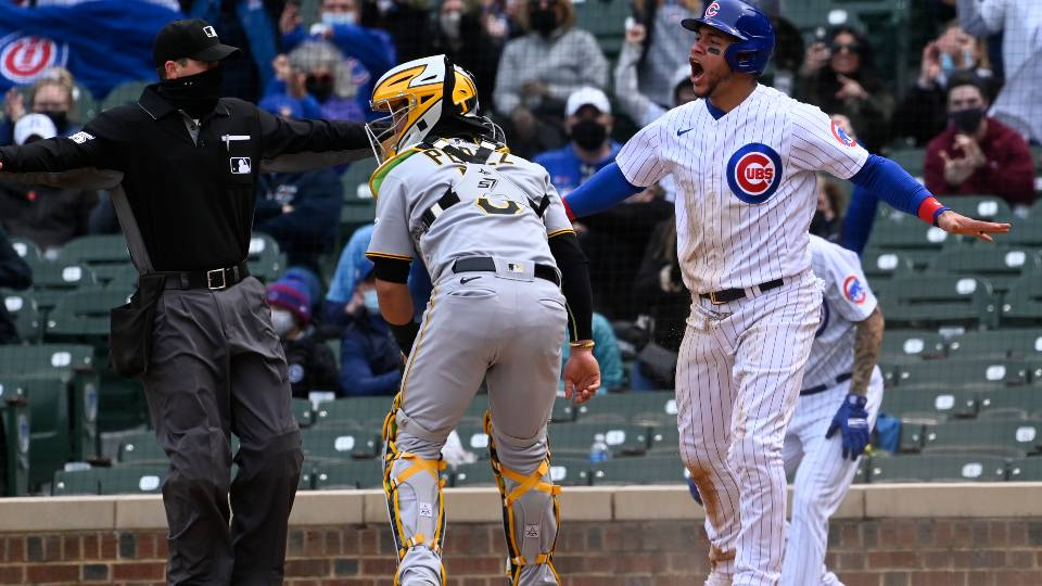 Chicago Cubs' Willson Contreras, right, reacts after he scored past Pittsburgh Pirates catcher Michael Perez (5) during the fourth inning of a baseball game, Saturday, May 8, 2021, in Chicago.