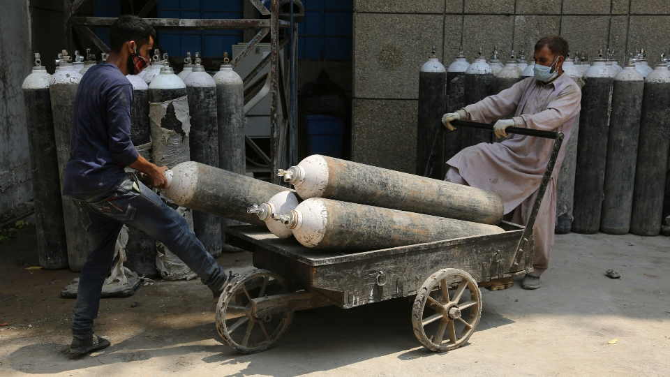 Workers load oxygen cylinders onto a hand cart to be carried inside the COVID-19 wards at a government run hospital in Jammu, India, Friday, May 7, 2021.