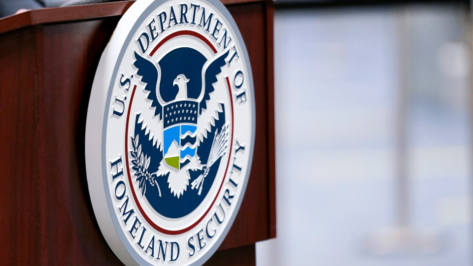 In this Nov. 20, 2020, file photo a U.S. Department of Homeland Security plaque is displayed a podium as international passengers arrive at Miami international Airport where they are screened by U.S. Customs and Border Protection in Miami.