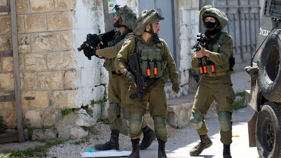 Israeli soldiers patrol after a soldier was killed when a rock thrown off a rooftop struck him in the head during an arrest raid