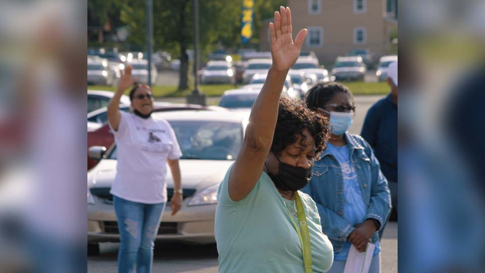A woman stretches out her hands in prayer Wednesday at the prayer vigil at the Bottom Dollar on Glenwood Avenue to kick off an anti violence campaign in the city (WKBN Photo/Joe Gorman)