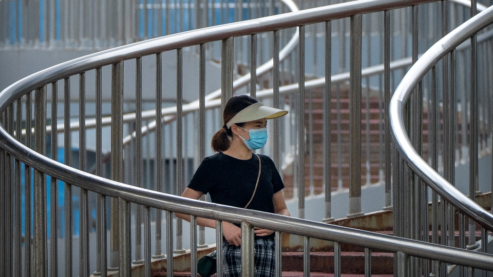 A woman wearing a face mask to protect against COVID-19 walk across a pedestrian bridge during the morning rush hour in Beijing, Wednesday, Aug. 4, 2021. China's worst coronavirus outbreak since the start of the pandemic a year and a half ago escalated Wednesday with dozens more cases around the country, the sealing-off of one city and the punishment of its local leaders. (AP Photo/Mark Schiefelbein)