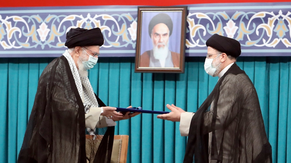 In this photo released by an official website of the office of the Iranian supreme leader, Supreme Leader Ayatollah Ali Khamenei, left, gives his official seal of approval to newly elected President Ebrahim Raisi in an endorsement ceremony in Tehran, Iran, Tuesday, Aug. 3, 2021. A portrait of the late revolutionary founder Ayatollah Khomeini hangs in the background. (Office of the Iranian Supreme Leader via AP)