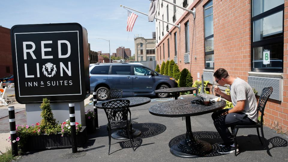 FILE - In this Aug. 25, 2016, file photo, New York Mets minor league pitcher Gary Cornish, of the Mets Class A New York-Penn League Brooklyn Cyclones, eats his habitual breakfast in the parking lot of the Red Lion Inn & Suites in New York where he and the other members of his team stay when the team is not traveling. Major League Baseball says its owners have agreed to begin providing housing to certain minor league players beginning in the 2022 season. ESPN, citing anonymous sources, first reported Sunday, Oct. 17, 2021, on the owners' decision, saying the league would require teams to provide housing either via stipends to fully cover housing or by arranging the lodging themselves. (AP Photo/Kathy Willens, File)