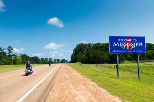Two motorcycles passing by the Mississippi State welcome sign al_1540207906321