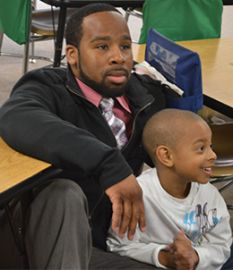 Leontae Couch sits with his son, Jayden, to start his kindergarten school day.