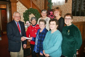 Ron Vendl, president of the Starke County Historical Society, accepts a check for $5,000 from Blanche Richardson, President of the Starke County Genealogical Society, while other members of the Genealogical Society look on,  Front Row:  Ron Vendl, Alice Dolezal, Blanche Richardson, Ida Kennedy, Susie Szynalski,  Back Row:  Audrey Kinezian and Patty Williams.