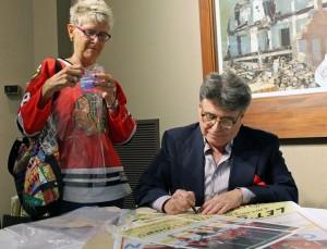 """Artist Mitch Markovitz signs copies of his """"Let's Go Hawks"""" South Shore Line poster at the Center for Visual and Performing Arts in Munster."""
