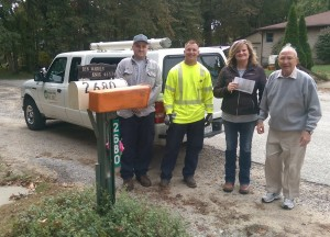 Employees Joel Metcalf, Chris Lawler and Jill Brown stand with KVREMC member Ben Warren after installing a reflective mailbox sign at his house.