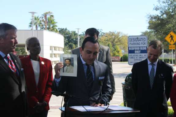 Andrae Bailey, CEO of the Central Florida Commission on Homelessness, holds up a photo of Nehemiah Woody, a homeless schizophrenic man who drowned himself earlier this year.