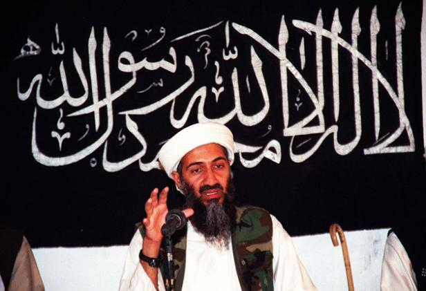 Osama Bin Laden speaking in front of the black flag of Islam