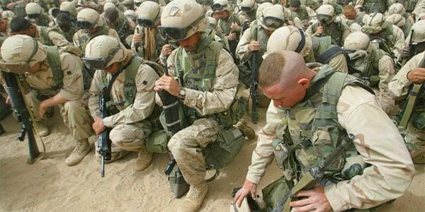 U.S. soldiers kneel in prayer