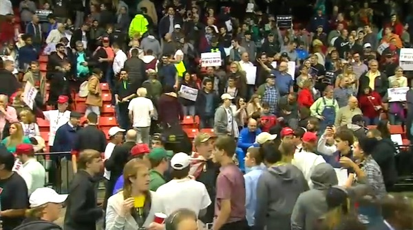 A stunned crowd of Donald Trump supporters loiters inside the University of Illinois-Chicago Pavilion after a security threat ended a political rally (Photo: NBC 5 Chicago screenshot)