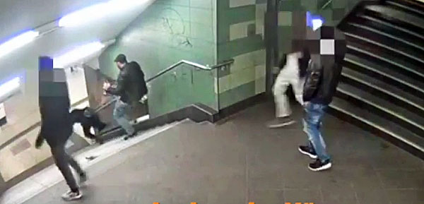 A man kicks a young woman down a flight of stairs in a Berlin, Germany, subway station. (Video screenshot)