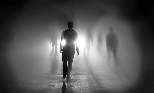 Silhouettes of people walking into light good evil darkness
