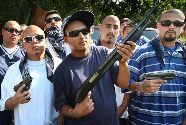 Gang members. Note blue theme in clothing or accessories. Photo credit Hispanically Speaking News