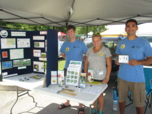WNY PRISM 2016 Crew (left to right: Tyler Christensen, Emily Dyett, Ian Sansone) at the Clarence Hollows Farmers' Market, staffing the WNY PRISM Educational Display. Photo Credit: Flora Leamer