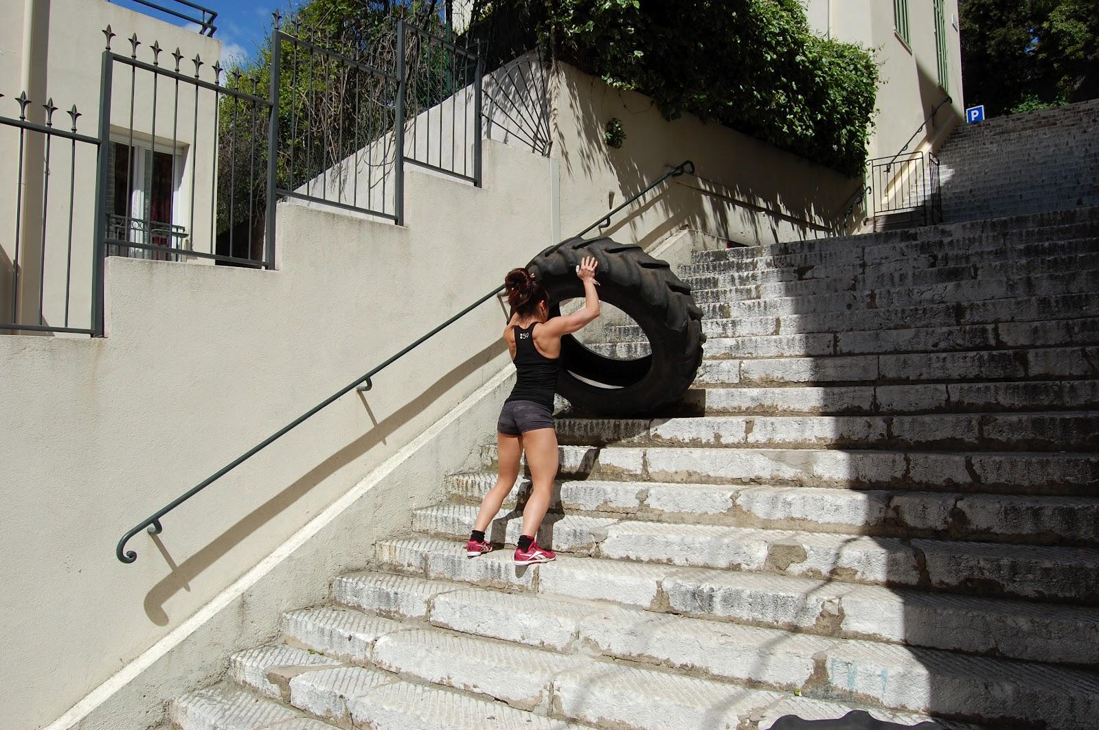 une crossfitteuse pousse un pneu dans les escaliers