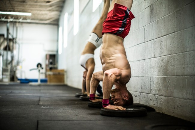 un crossfitteur et une crossfitteuse en train de faire un handstand pushups