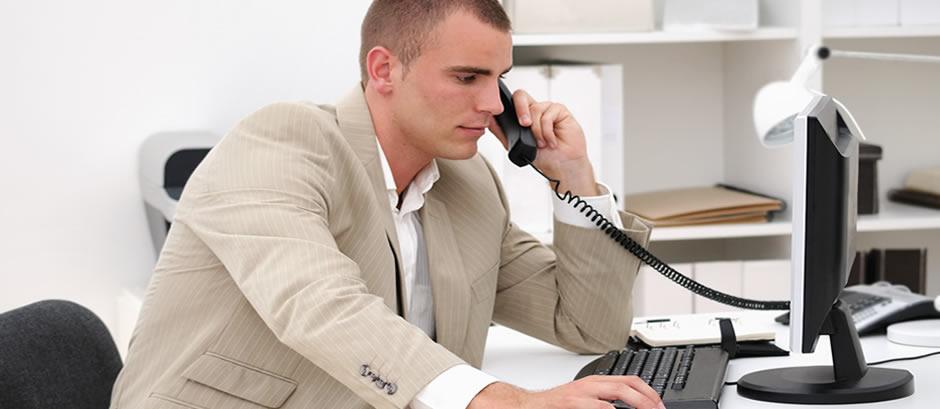Une personne assise au bureau en train de telephoner