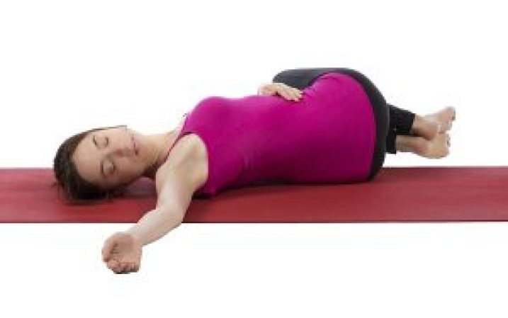 Young woman is stretching her spine during yoga.
