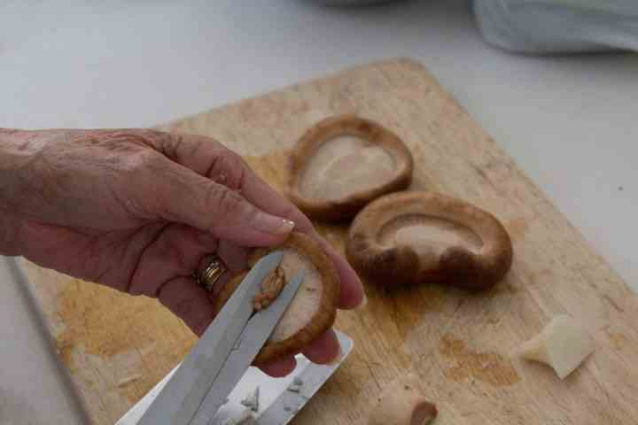 Using scissors to remove stems from mushrooms