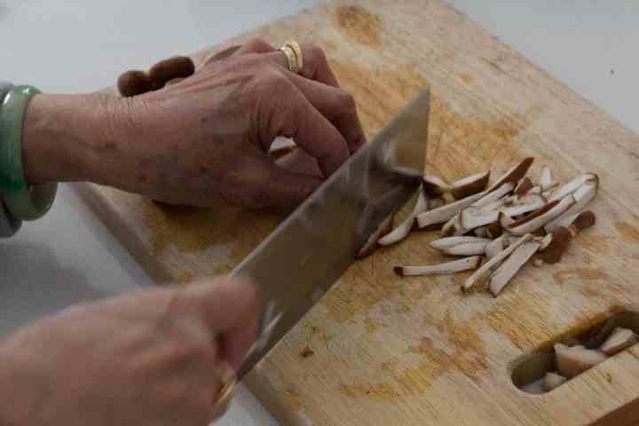 Slicing shiitake mushrooms on a chopping board