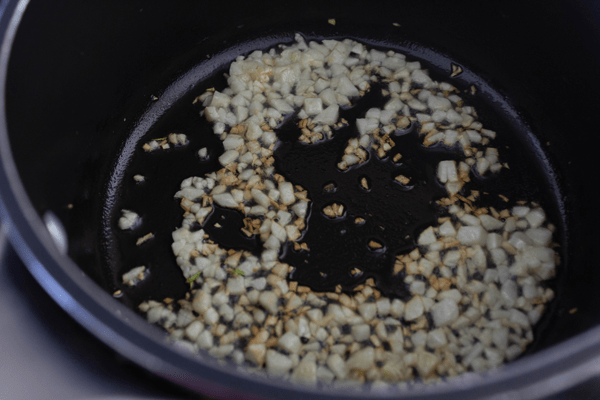 Finely chopped garlic being browned in a small pot with oil