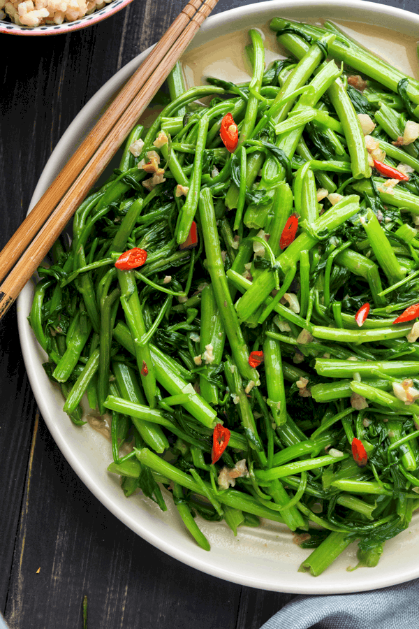 Close up of stir fried water spinach on a plate with chopsticks to the side