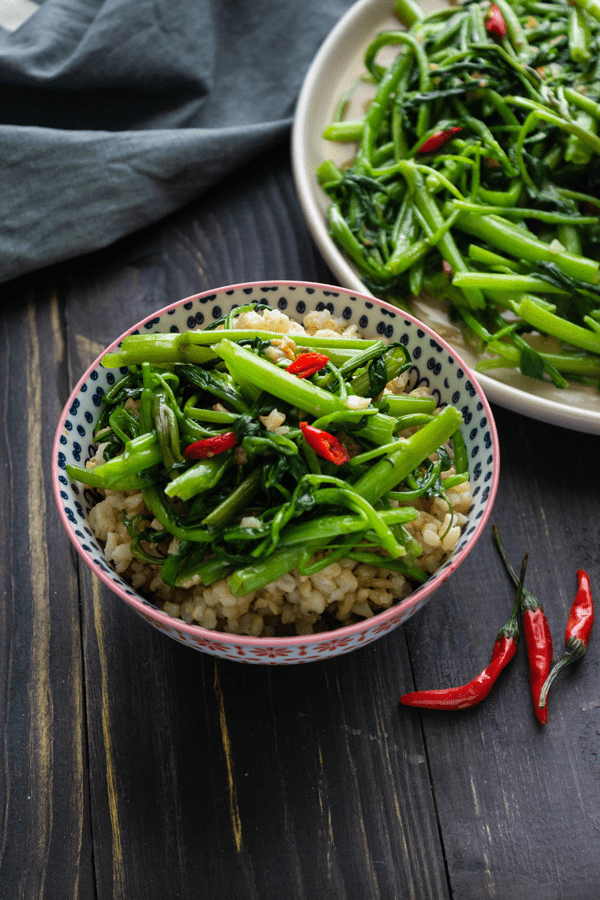 Stir fried water spinach on a bowl of rice