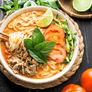 Satay beef noodle soup in a bowl on a table