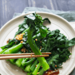 Chopsticks holding Chinese broccoli on a plate