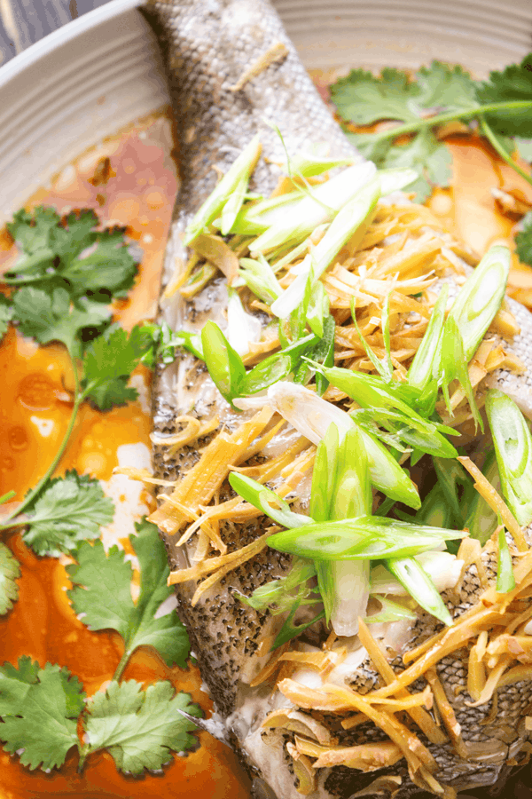 Close up of fish with ginger and shallots on soy