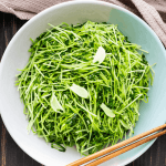 Pea shoots with garlic in a bowl with chopsticks