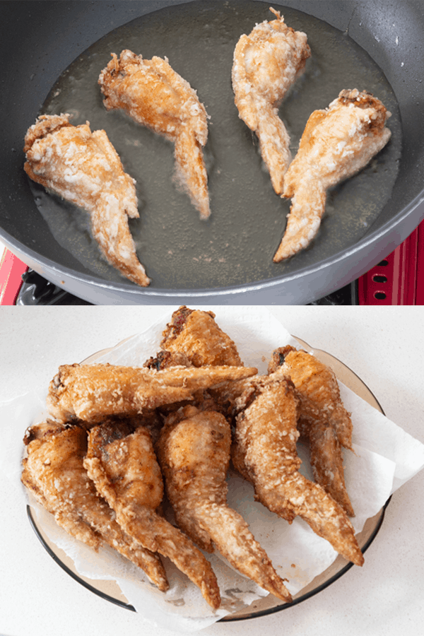 Chicken wings being fried in a wok with oil and wings already fried resting on a plate