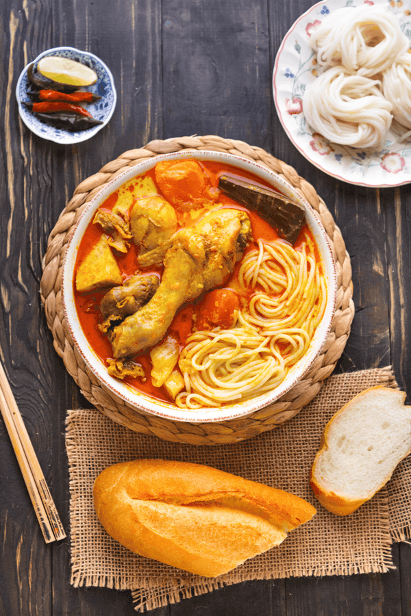 Vietnamese chicken curry and noodles in a bow with a plate of rice noodles, chopsticks and a baguette