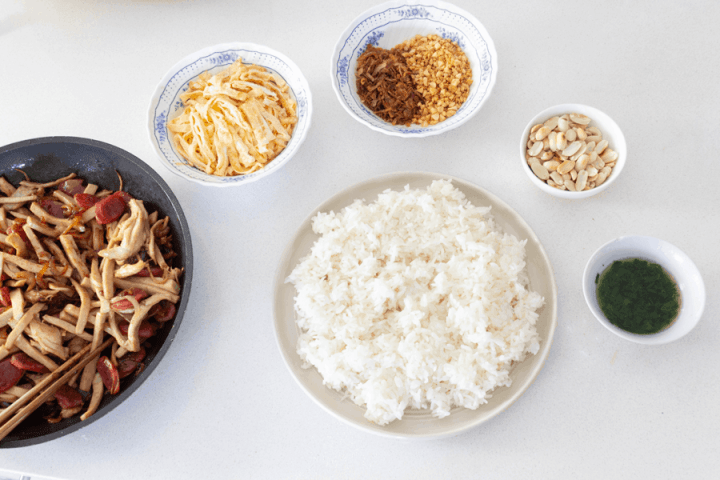 Glutinous rice, omelette strips, fried onion and garlic, roasted peanuts, spring onion oil and stir fried Chinese sausages and Vietnamese ham in dishes