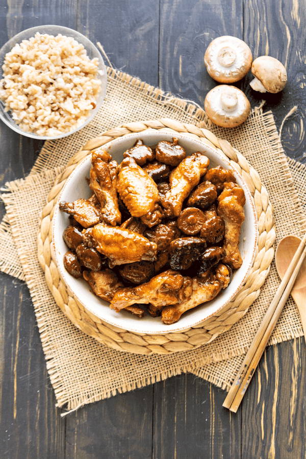 Chicken wings and mushrooms in a bowl with a rice bowl and chopsticks beside it