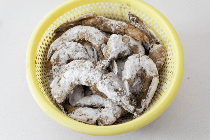 Prawns coated in potato starch in a colander