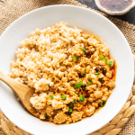 Tofu and mince on a plate with brown rice and a wooden spoon