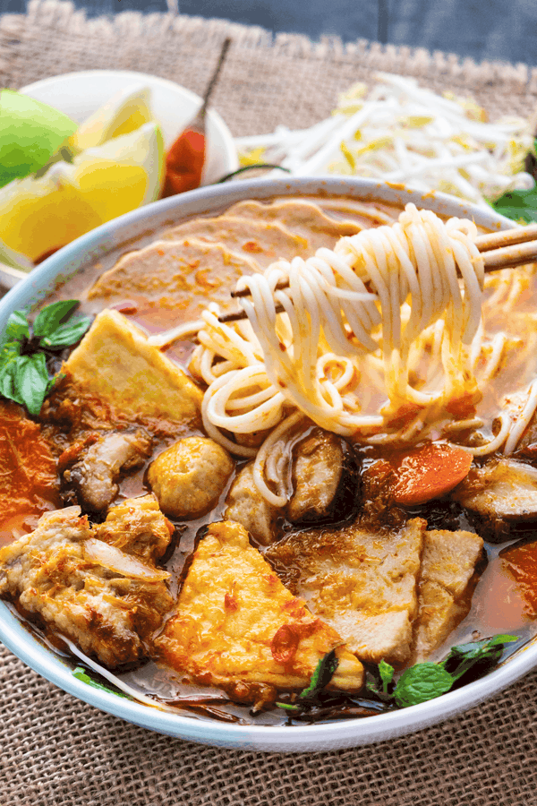 Noodles held up by chopsticks in a bowl of soup with mushrooms, carrots and mint