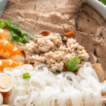 Rice noodles with pork mince, pork slices, prawns, quail eggs and spring onions in a bowl