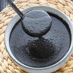 Black sesame soup in a bowl with a ladle