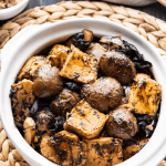 Bean curd and mushrooms in a pot with bowls of rice