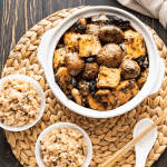 Bean curd and mushrooms in a pot with bowls of rice, a spoon and chopsticks