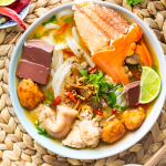 Banh Canh Cua in a bowl with a dish of chilis and half a lime above