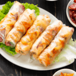 Bo bia on lettuce on a plate with dried shrimp and Chinese sausages in a dish