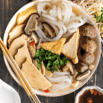 Banh Canh Chay in a bowl with chopsticks surrounded by herbs and a dish of sauce